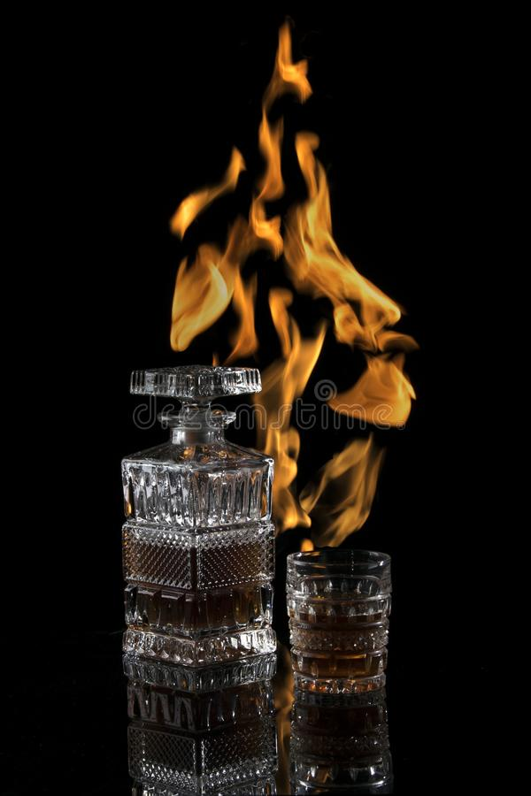 Botella y vidrio de escocés en un fondo oscuro con las llamas imágenes de archivo libres de regalías