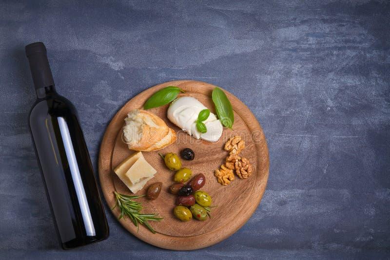 Botella y vidrio de vino con queso, las aceitunas, el pan, las nueces y el romero en fondo oscuro Concepto del vino y de la comid imagen de archivo