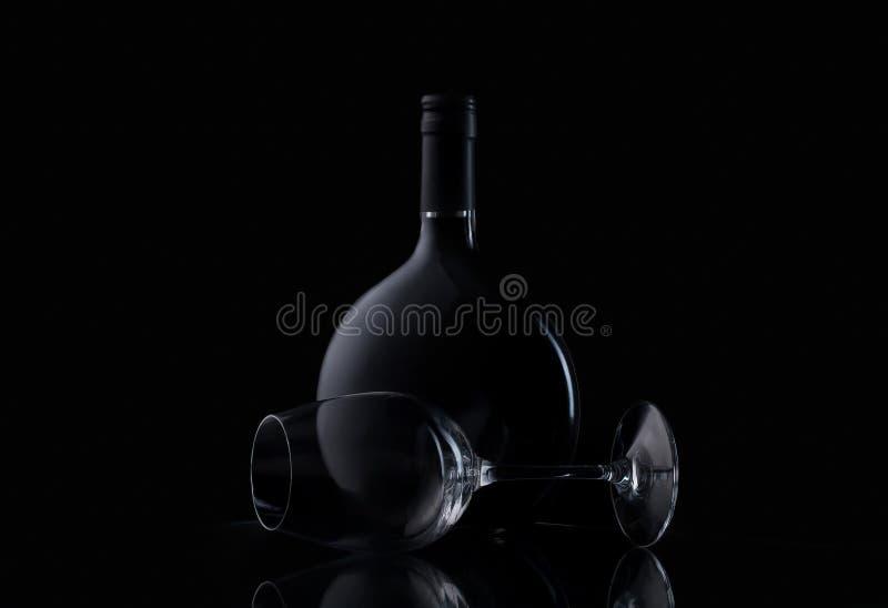 Botella y vidrio de vino en fondo negro fotografía de archivo libre de regalías