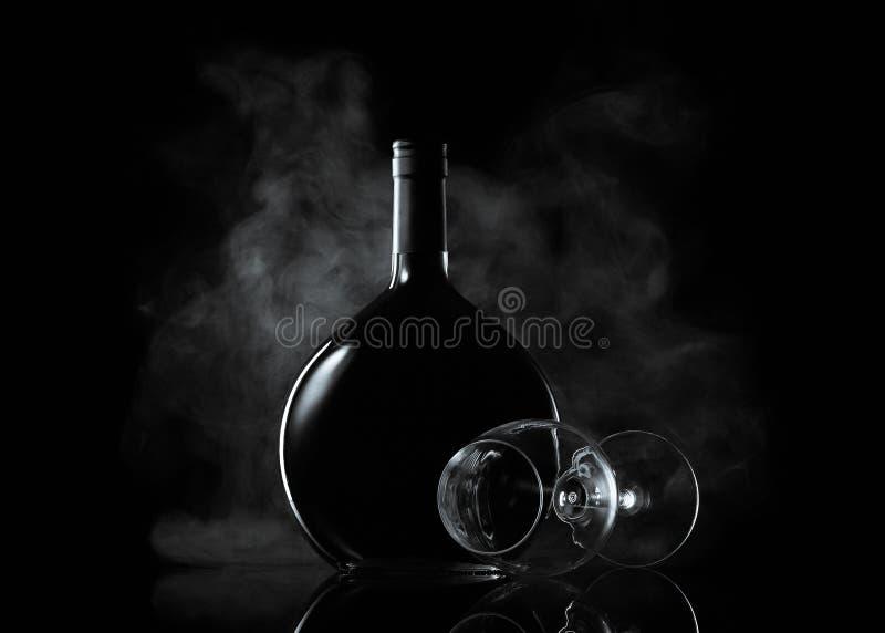 Botella y vidrio de vino en humo imagen de archivo libre de regalías