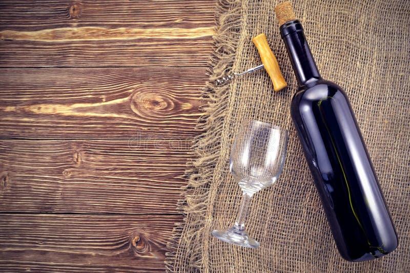 Botella y vidrio de vino en los tableros de madera del fondo imagen de archivo libre de regalías