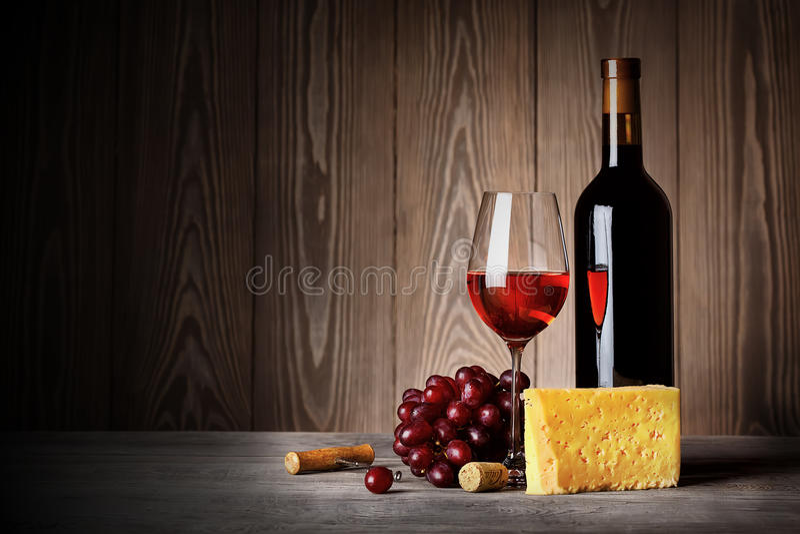 Botella y vidrio de vino rojo con las uvas del queso foto de archivo libre de regalías