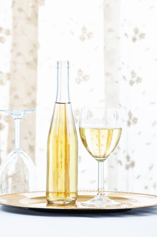 Botella y vidrio del vino blanco en una placa de oro delante de una ventana con las cortinas imagenes de archivo