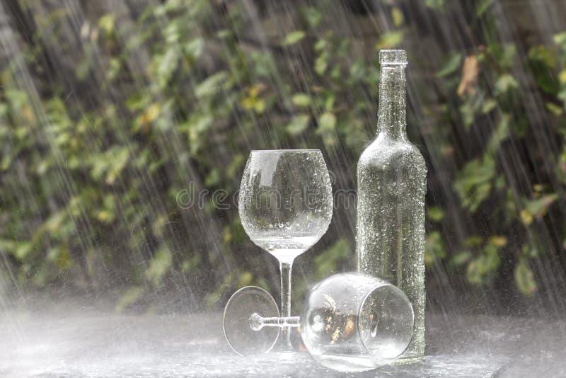 Botella y vidrios de vino en lluvia del verano fotos de archivo libres de regalías