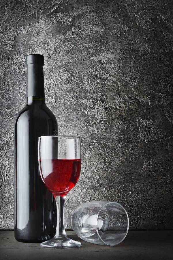 Botella y vidrios de vino rojo para probar en sótano oscuro foto de archivo