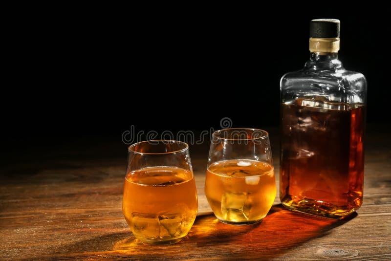 Botella y vidrios de whisky en la tabla de madera contra fondo oscuro imagen de archivo libre de regalías