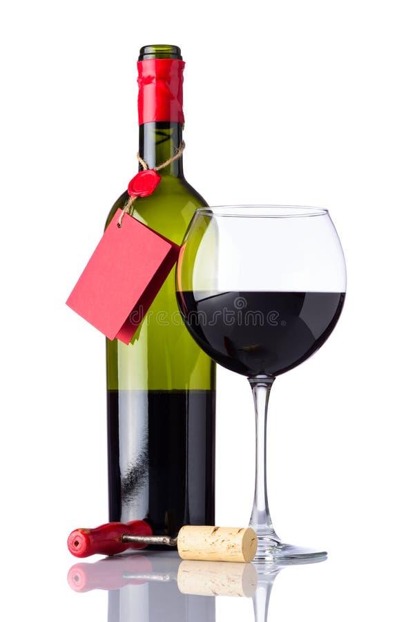 Botella y vino rojo de cristal en el fondo blanco imágenes de archivo libres de regalías