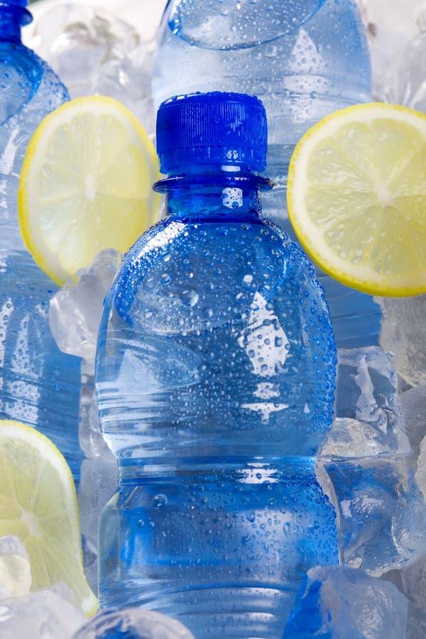 Botellas azules de agua en hielo foto de archivo