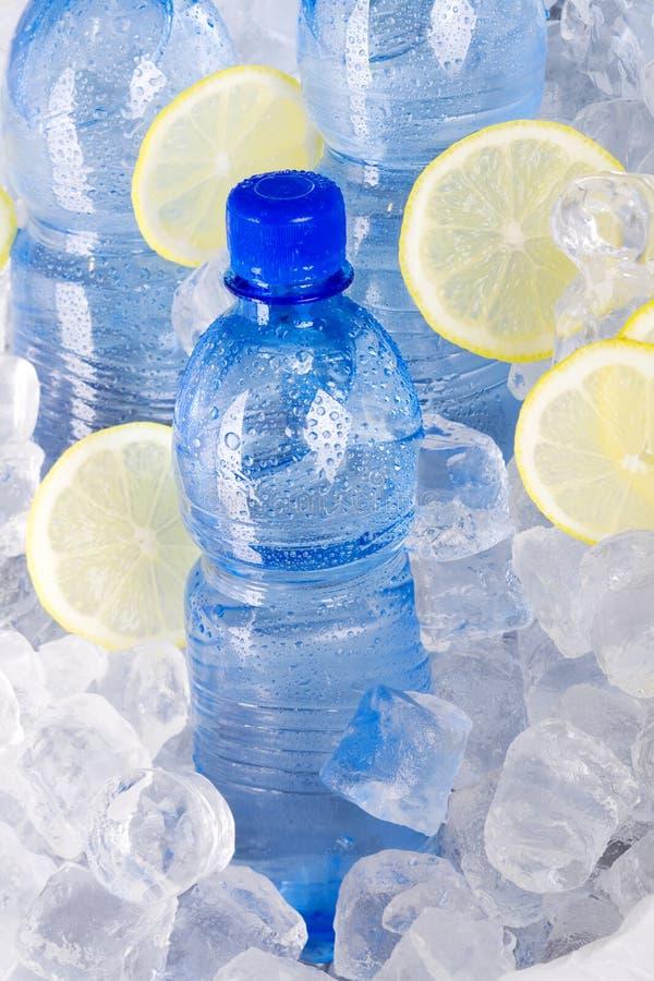 Botellas azules de agua en hielo imágenes de archivo libres de regalías