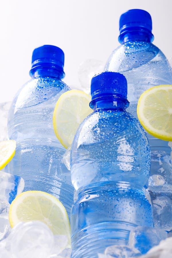Botellas azules de agua en hielo fotografía de archivo libre de regalías