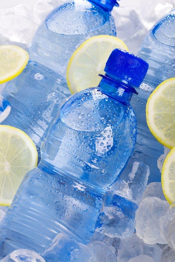 Botellas azules de agua en hielo fotografía de archivo