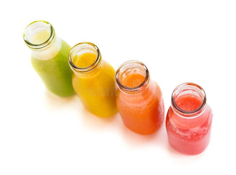 Botellas coloridas del jugo del smoothie en el fondo blanco fotos de archivo