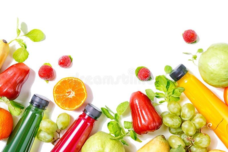 Botellas coloridas hermosas del jugo con la frontera de las frutas tropicales aislada en el fondo blanco Concepto de la comida de fotografía de archivo libre de regalías