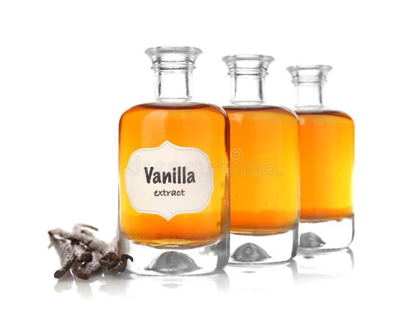 Botellas con el extracto aromático y las habas de vainilla secas fotos de archivo