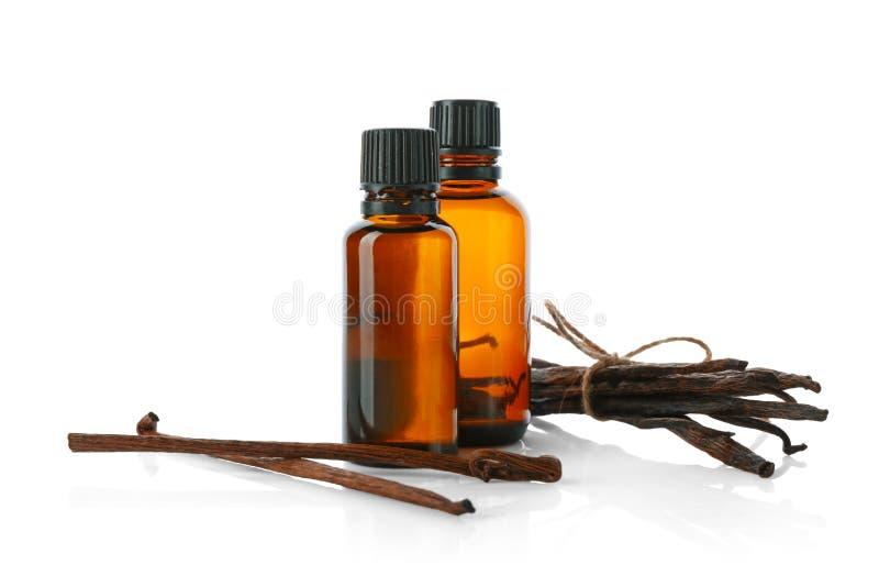 Botellas con el extracto y los palillos de vainilla fotografía de archivo
