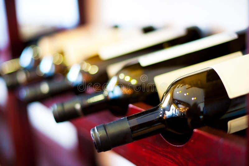Botellas con el vino en el regimiento en bodega foto de archivo