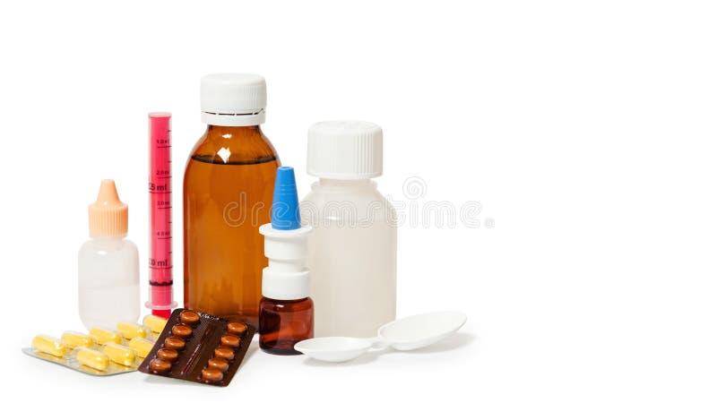 Botellas con la medicina, espray nasal Tosa el jarabe, el jarabe anti-pirético y los descensos de nariz en el fondo blanco Medica imágenes de archivo libres de regalías