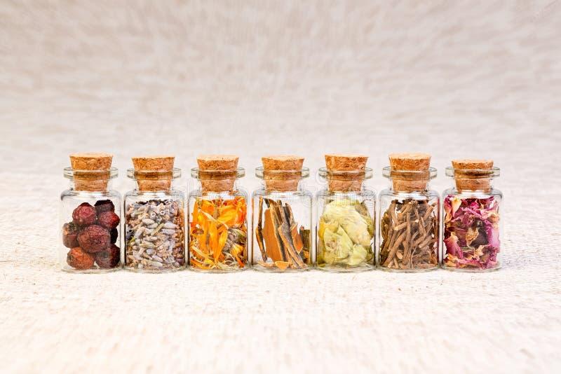 Botellas con las hierbas usadas en homeopatía fotos de archivo