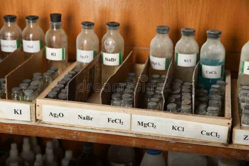 Botellas con las soluciones de NaBr, FeCl2, MgCl2 en el estante del gabinete químico imagen de archivo libre de regalías