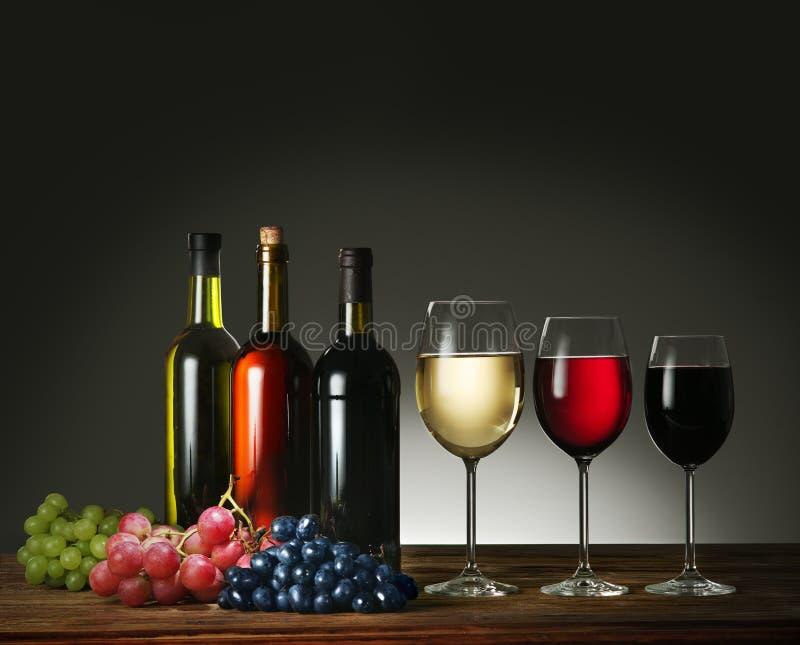 Botellas, copas de vino y uvas de vino foto de archivo