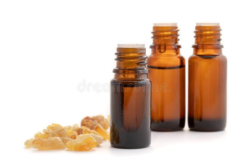 Botellas de aceite esencial con la resina del incienso en un fondo blanco foto de archivo