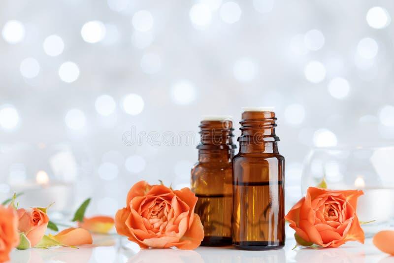Botellas de aceite esencial con las flores color de rosa en la tabla blanca con efecto del bokeh Balneario, aromatherapy, salud,  imagen de archivo