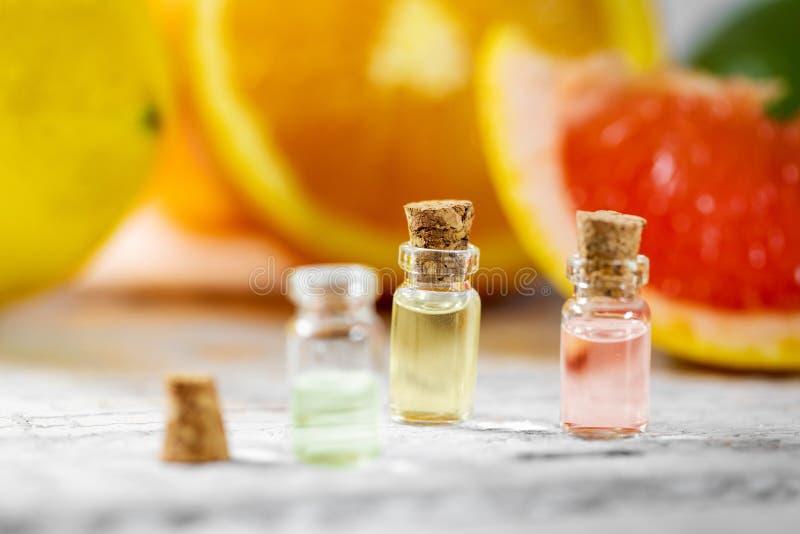 Botellas de aceite esencial de la fruta cítrica en fondo de la fruta foto de archivo