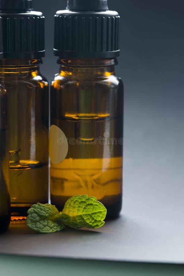 Botellas de aceite esencial y hojas de la hierbabuena aisladas en el fondo gris, concepto del aromatherapy fotografía de archivo
