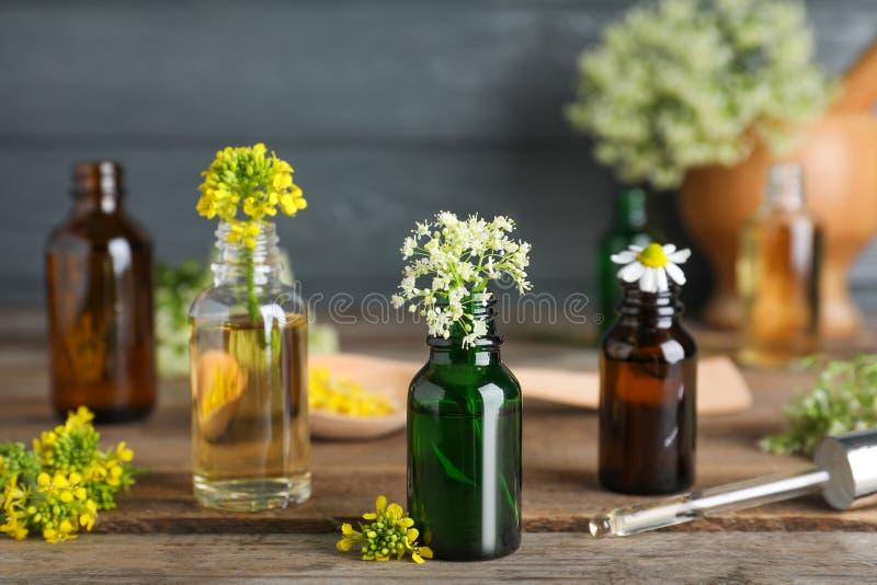 Botellas de aceites esenciales, de pipeta y de flores imágenes de archivo libres de regalías