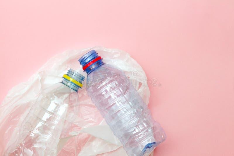 Botellas de agua plásticas arrugadas y la bolsa de plástico blanca listas para reciclar aislada en el fondo rosado, visión superi fotos de archivo