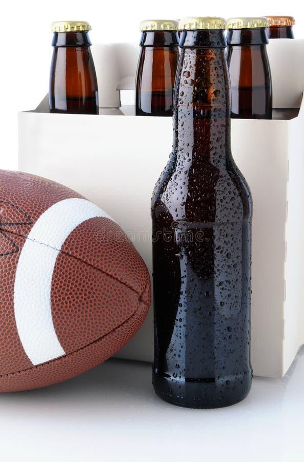 Botellas de cerveza con fútbol americano fotografía de archivo