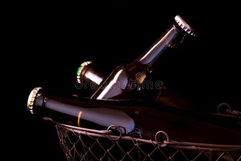 Botellas de cerveza en un claroscuro negro del fondo en una cesta vieja de la malla metálica imagen de archivo