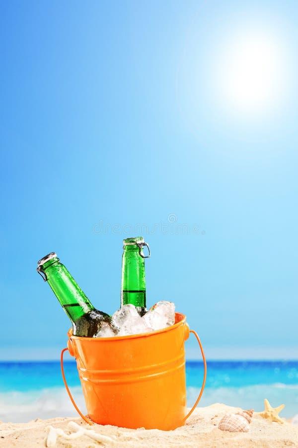 Botellas de cerveza en un cubo de hielo en la arena en una playa fotos de archivo