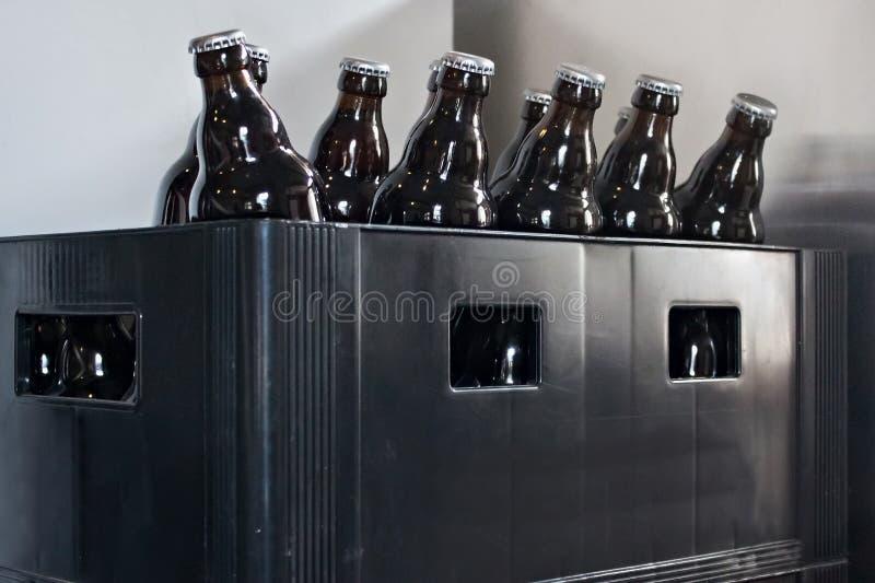 Botellas de cerveza en una caja plástica vieja imagenes de archivo