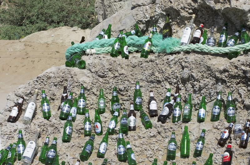 Botellas de cerveza vacías maravillosamente presentadas en un canto rodado enorme en un tiempo soleado fotografía de archivo