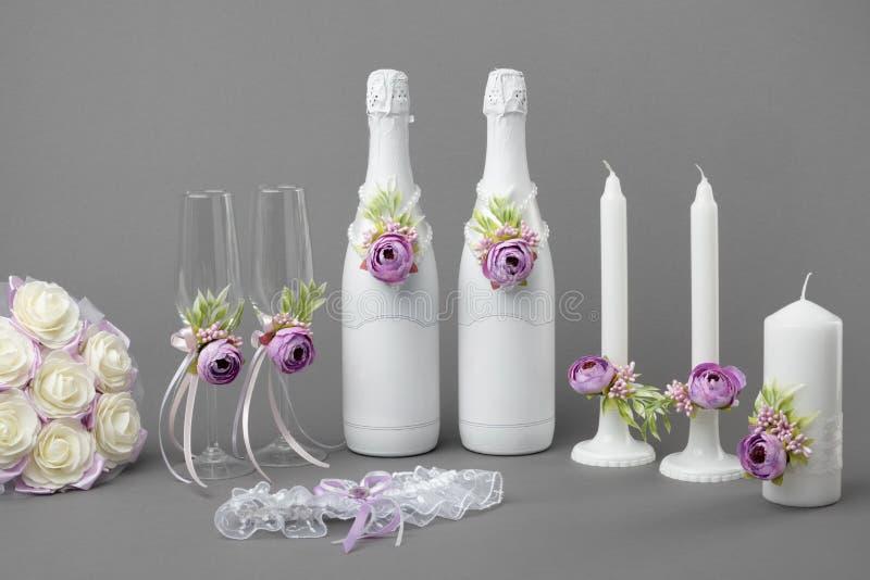 Botellas de champán con las etiquetas, las copas de vino, las velas, las novias liga y el ramo en blanco de la flor imagen de archivo libre de regalías