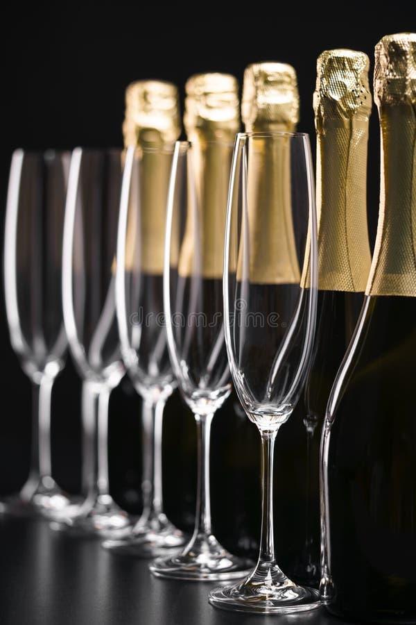 Botellas de champán y de vidrios vacíos en un fondo negro SE imagenes de archivo
