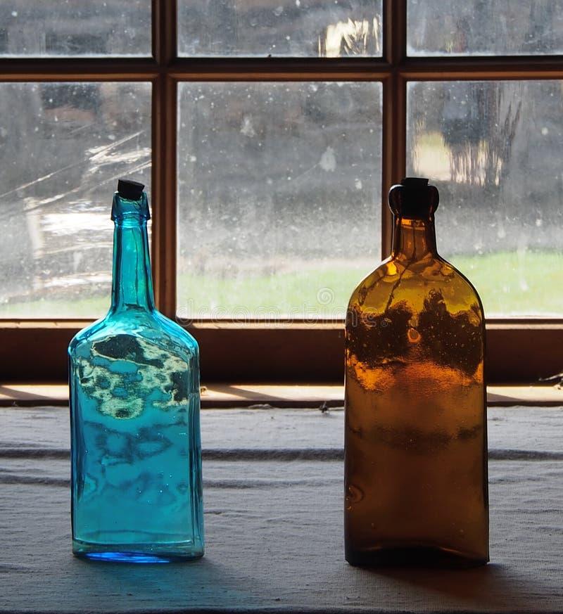 Botellas de cristal antiguas en ventana imagenes de archivo
