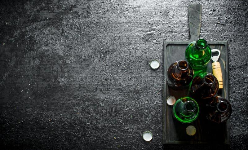 Botellas de cristal de cerveza en una tabla de cortar negra foto de archivo libre de regalías