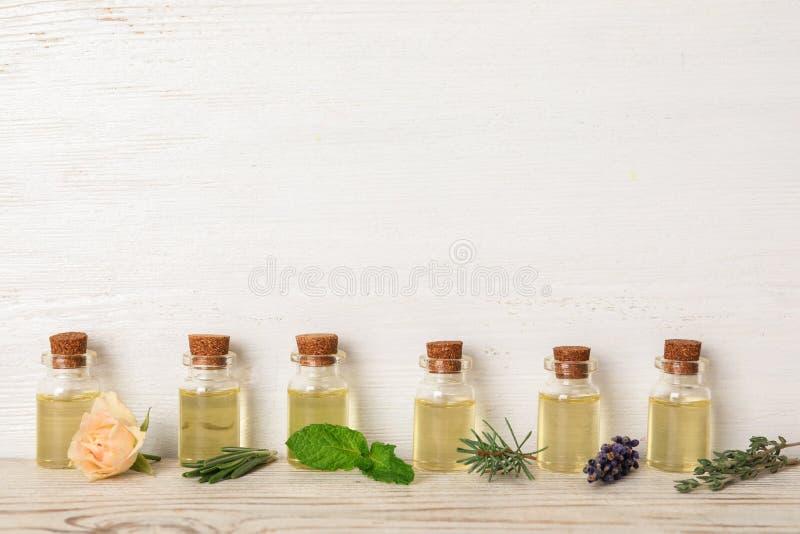Botellas de cristal con diversos aceites esenciales e hierbas fotografía de archivo