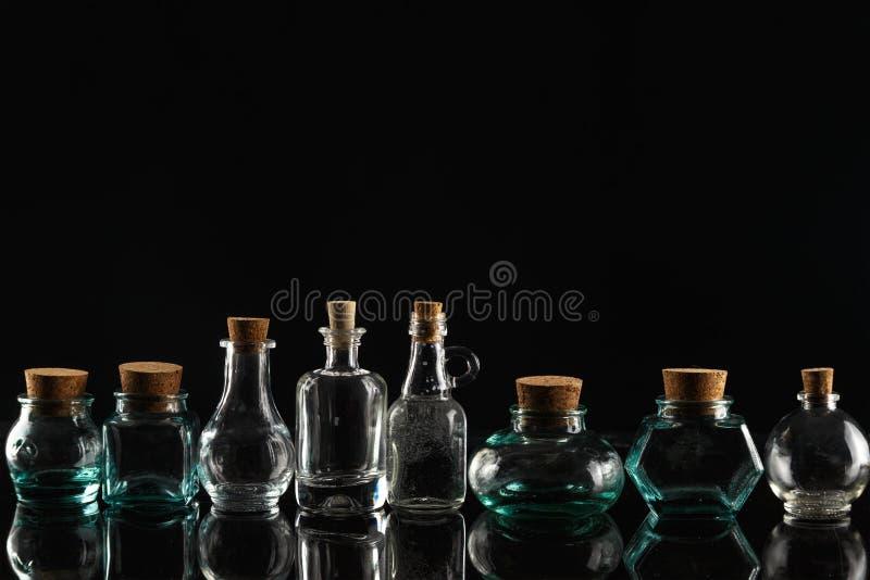 Botellas de cristal de diversos formas y tamaños en un fondo negro foto de archivo libre de regalías
