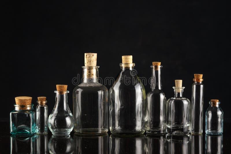 Botellas de cristal de diversos formas y tamaños en un fondo negro fotografía de archivo libre de regalías