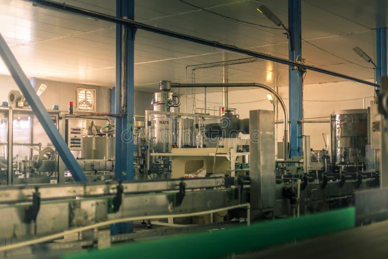 Botellas de cristal en la línea automática del transportador en la fábrica del champán, de la cerveza o del vino imagen de archivo