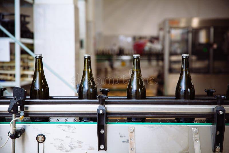 Botellas de cristal en la línea automática del transportador en la fábrica del champán o del vino Planta para embotellar las bebi imagenes de archivo