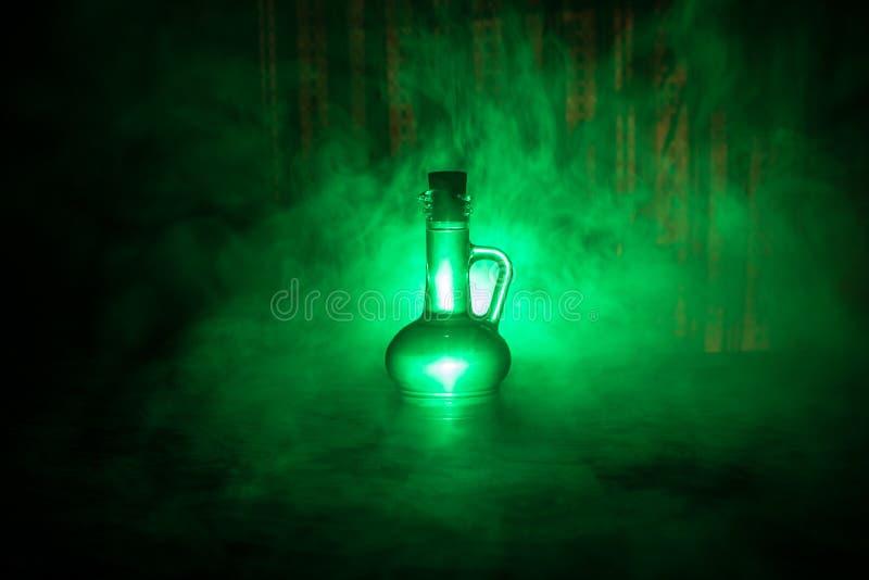Botellas de cristal de la antigüedad y del vintage en fondo de niebla oscuro con la luz Veneno o concepto del líquido de la magia fotografía de archivo libre de regalías