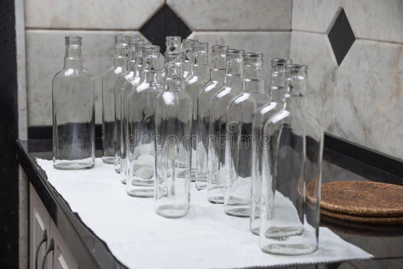 Botellas de cristal vacías en la cocina a llenar de la bebida fotos de archivo