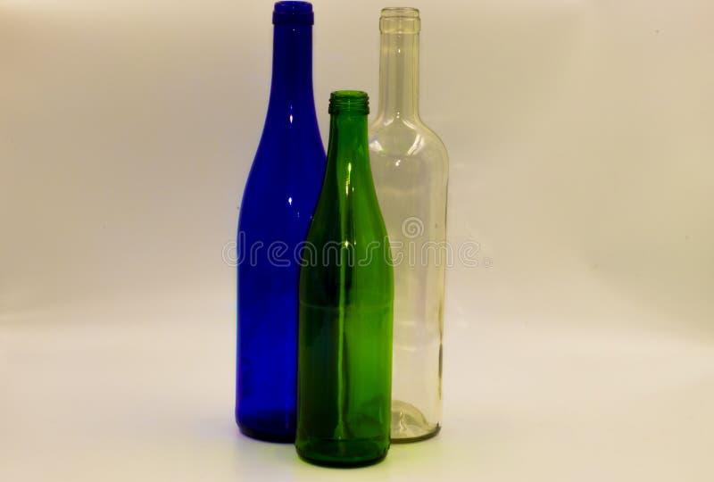 Botellas de cristal vacías en un fondo blanco imagenes de archivo