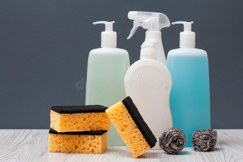 Botellas de detergente y de esponjas en fondo gris imagen de archivo libre de regalías
