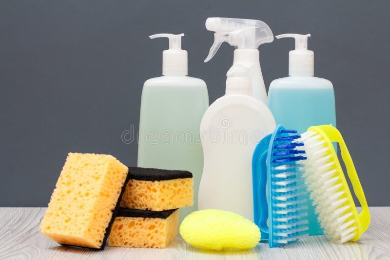 Botellas de líquido, de cepillos y de esponjas del lavaplatos en fondo gris imagen de archivo libre de regalías