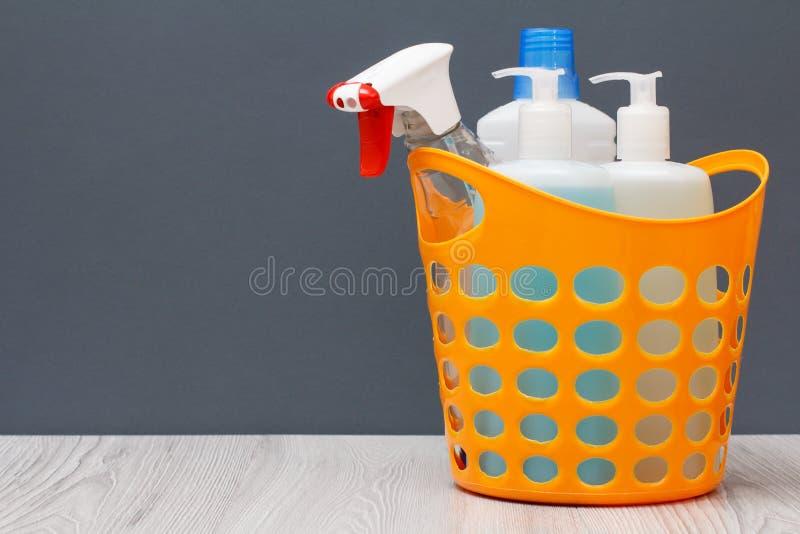 Botellas de líquido del lavaplatos en una cesta plástica en fondo gris fotos de archivo libres de regalías